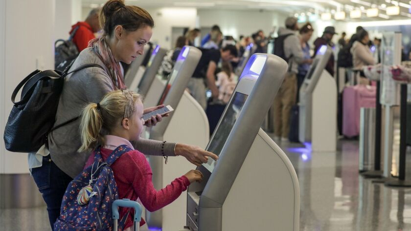 Katy Von Treskow and her daughter use a check-in kiosk last year at Los Angeles International Airport. More airlines are adding such stations to help reduce wait times.
