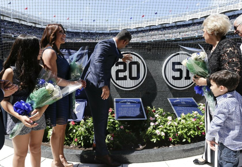 Accompanied by family members, former New York Yankees catcher Jorge Posada touches a plaque with his jersey number on a wall in Monument Park during a ceremony retiring his number before a baseball game against the Cleveland Indians, Saturday, Aug. 22, 2015, in New York. (AP Photo/Julie Jacobson)