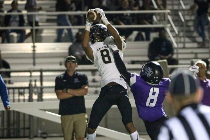 Calabasas wide receiver Amoni Butler catches a touchdown pass over Rancho Cucamonga's Jordan Webb during the second quarter of Thursday's game.
