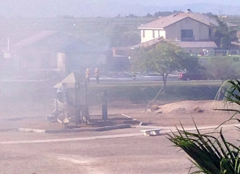 Smoke rises over a residential neighborhood in Imperial after the crash of a military jet.
