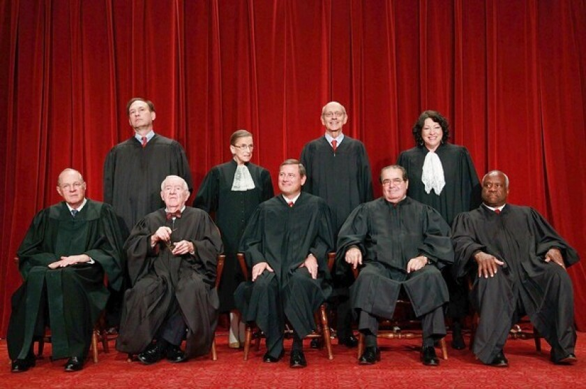 Sitting in the front row, second from the right, Antonin Scalia poses with his Supreme Court colleagues on Sept. 29. Scalia was appointed to the high court by President Reagan in 1986.