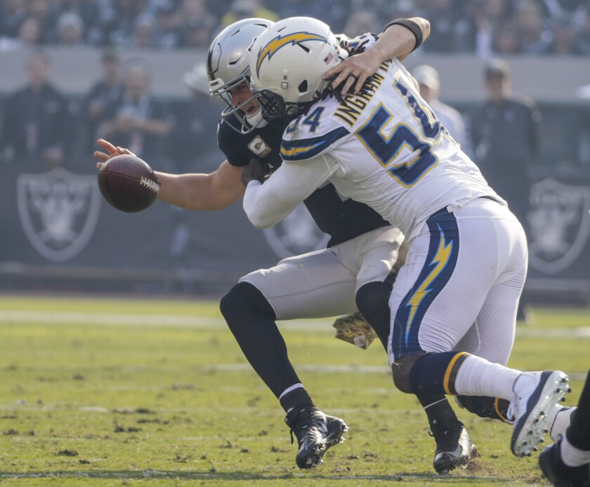 Chargers linebacker Melvin Ingram III knocks the ball loose as he sacks Oakland Raiders quarterback Derek Carr in the second quarter at Oakland-Alameda County Coliseum on Sunday.