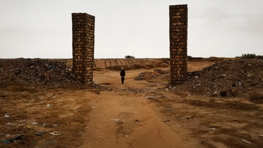 Chamseddine Marzoug passes through two brick columns that mark the entrance to the donated cemetery where he buries migrants, between olive groves and the town dump. He is trying to raise money to build a new cemetery.
