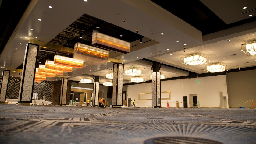 Construction workers finish gluing carpet this week in the main casino room of the revamped Hollywood Park Casino off of West Century Boulevard in Inglewood.