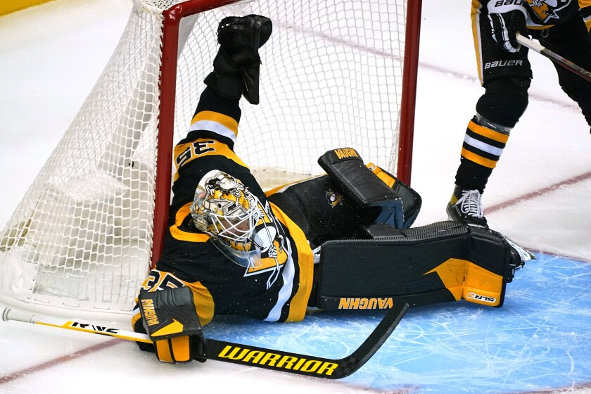 Pittsburgh Penguins goaltender Tristan Jarry sprawls across the goal crease during the first period of a preseason NHL hockey game against the Detroit Red Wings in Pittsburgh, Sunday, Oct. 3, 2021.(AP Photo/Gene J. Puskar)