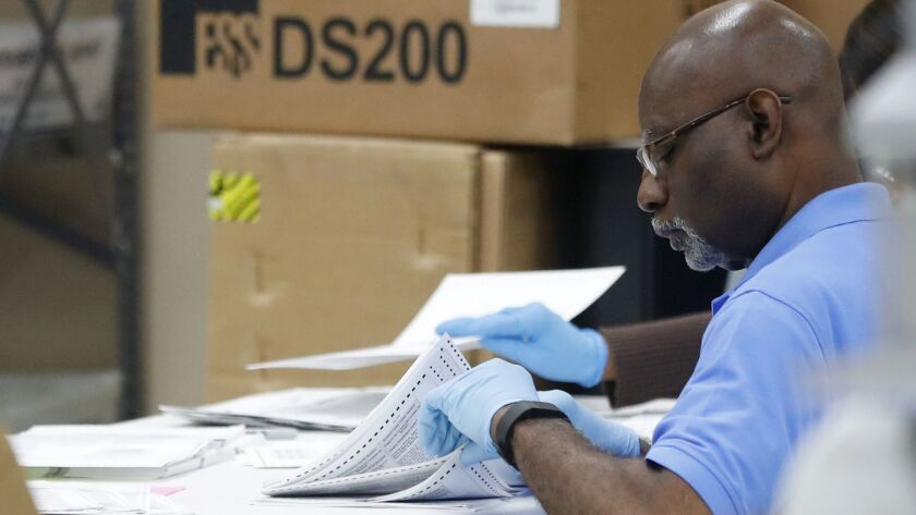 An employee at the Broward County Supervisor of Elections office examines ballots during a recount,