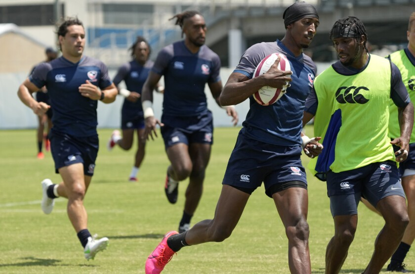 Perry Baker, center right, of the U.S. rugby sevens team runs with a ball during a training session at the Olympics.