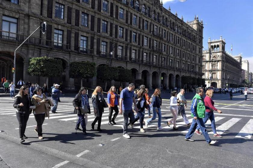 Cientos de personas evacuan los edificios en el zócalo de la capital de México tras un sismo de magnitud 6,5 que se produjo este viernes, en Ciudad de México (México). EFE