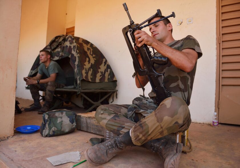 A French soldier from the 21st Marine Infantry Regiment prepares a FAMAS machine gun at a Malian army airbase near Bamako, Mali's capital.