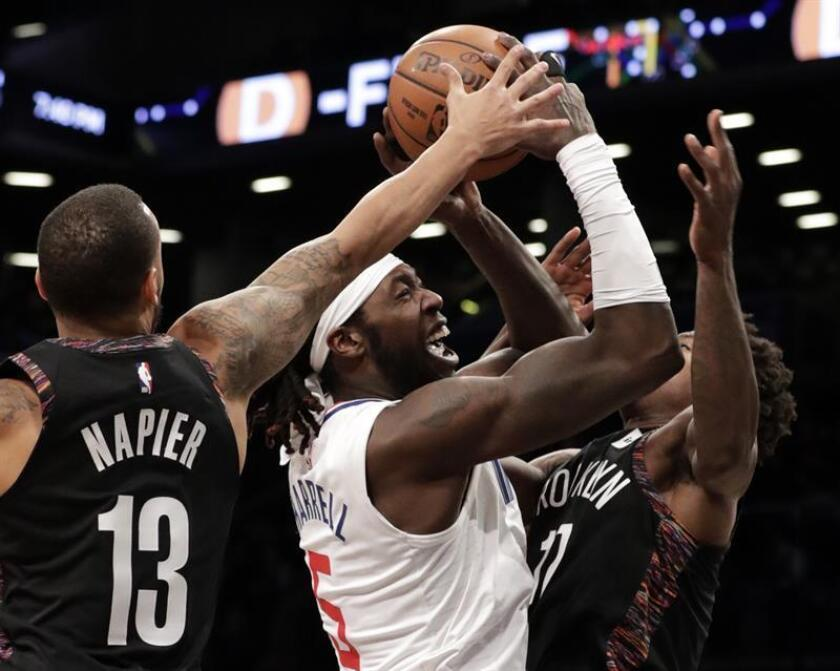 LA Clippers forward Montrezl Harrell (C) fights to control the ball under the basket while being defended by Brooklyn Nets guard Shabazz Napier (L) and teammate Brooklyn Nets forward Ed Davis (R) in the second half of the game between the Los Angeles Clippers and the Brooklyn Nets at Barclays Center in Brooklyn, New York, USA, 17 November 2018. EPA-EFE/JASON SZENES