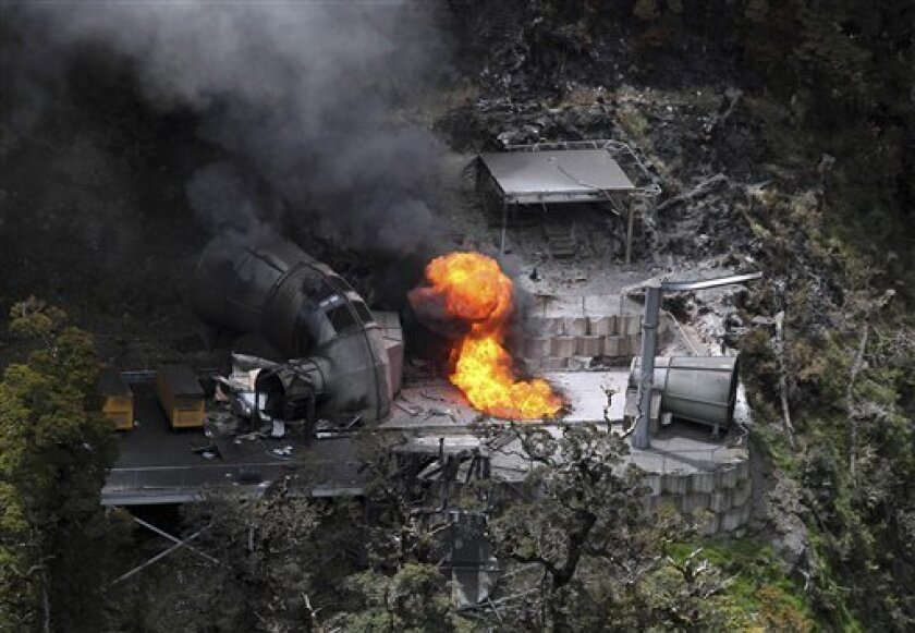 FILE - In this Nov. 30, 2010 file photo, flames burn from a ventilation shaft above the Pike River mine which has fatally trapped 29 miners and contractors in Greymouth, New Zealand. A New Zealand judge Friday, July 5, 2013 ordered the coal mining company Pike River Coal to pay compensation to the families of 29 miners killed in the 2010 methane explosion. (AP Photo/NZPA, Iain McGregor, File) NEW ZEALAND OUT