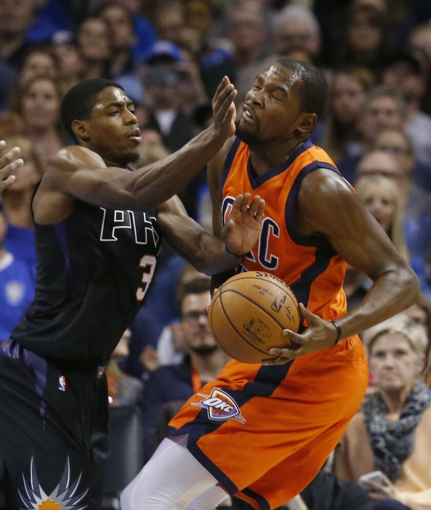 Oklahoma City Thunder forward Kevin Durant, right, is fouled by Phoenix Suns guard Brandon Knight (3) in the first quarter of an NBA basketball game in Oklahoma City, Sunday, Nov. 8, 2015. (AP Photo/Sue Ogrocki)