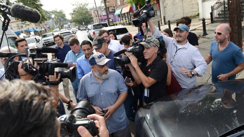 Mohammad Rahami, center left, speaks to reporters in Elizabeth.