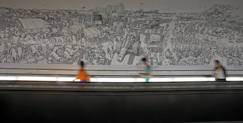 A moving walkway in the Montparnasse Metro station in Paris carries commuters past Joe Sacco's massive cartoon mural depicting the first day of the 1916 Battle of the Somme.