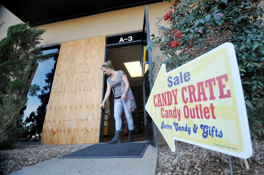 """Candy Crate general manager Randi Caporale examines the boarded up window where two men wearing hooded sweatshirts broke the window to gain access inside on Friday, Jan 3, 2014, in Hesperia, Calif. """"Nothing was taken. They probably saw the empty cash register and took off when the alarm went,"""" said Caporale. (AP Photo/Daily Press, David Pardo)"""