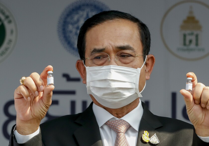 FILE - In this Feb. 24, 2021, file photo, Thai Prime Minister Prayuth Chan-ocha holds samples of Sinovac vaccine during a ceremony to mark the arrival of 200,000 doses of the Sinovac vaccine shipment at Suvarnabhumi airport in Bangkok, Thailand. Prayuth was not particularly lauded for his leadership last year against the coronavirus, but for much of 2020 Thailand fought the disease to a standstill, with low infection and death rates envied by more developed countries. (AP Photo/Sakchai Lalit, File)