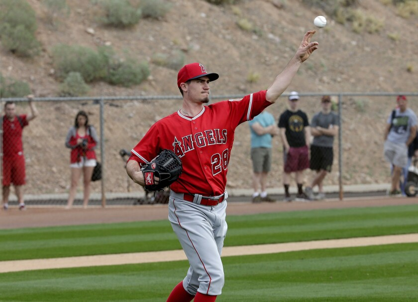 Angels starting pitcher Andrew Heaney throws to first as fans watch along the fence during spring training baseball workouts.