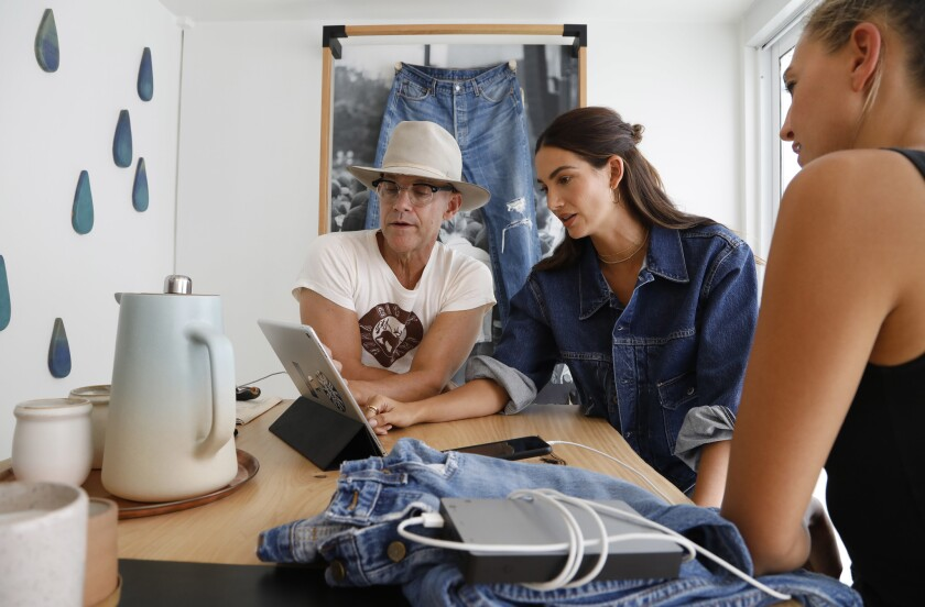 LOS ANGELES- August 17, 2018: Model Lily Aldridge, center, designs a pair of jeans on an iPad along