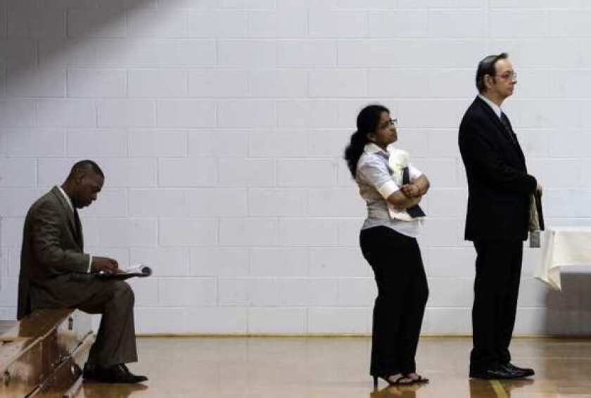 Job-seekers wait in a line at a job fair in Southfield, Mich., in 2011.