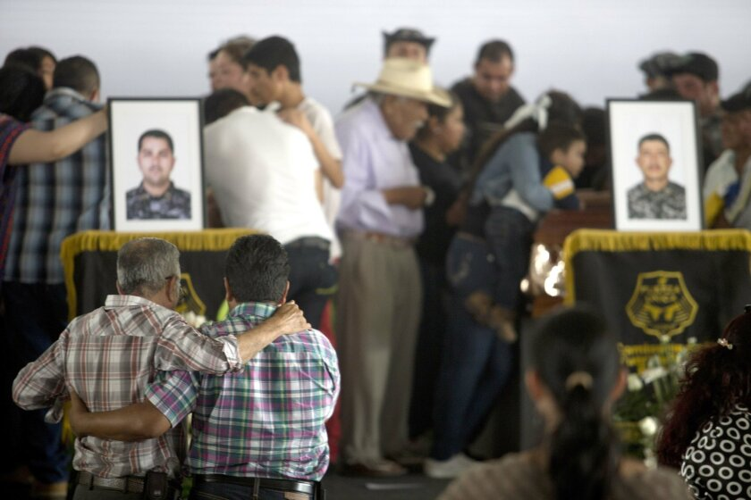 Mourners comfort each other during a ceremony to honor slain policemen in Tlaquepaque, Mexico, Wednesday, April 8, 2015. On Monday, the Jalisco New Generation drug cartel stopped a police convoy on a rural highway and opened fire, killing 15 officers and wounding five in the bloodiest single attack