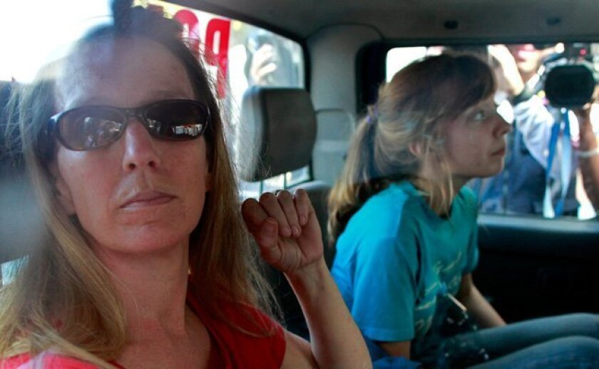 Corinna Lankford, left, and her daughter Nicole Lankford, 18, both of Middleton, Idaho, sit in a police truck before being taking back to jail in Port-au-Prince, Thursday, Feb. 4, 2010.