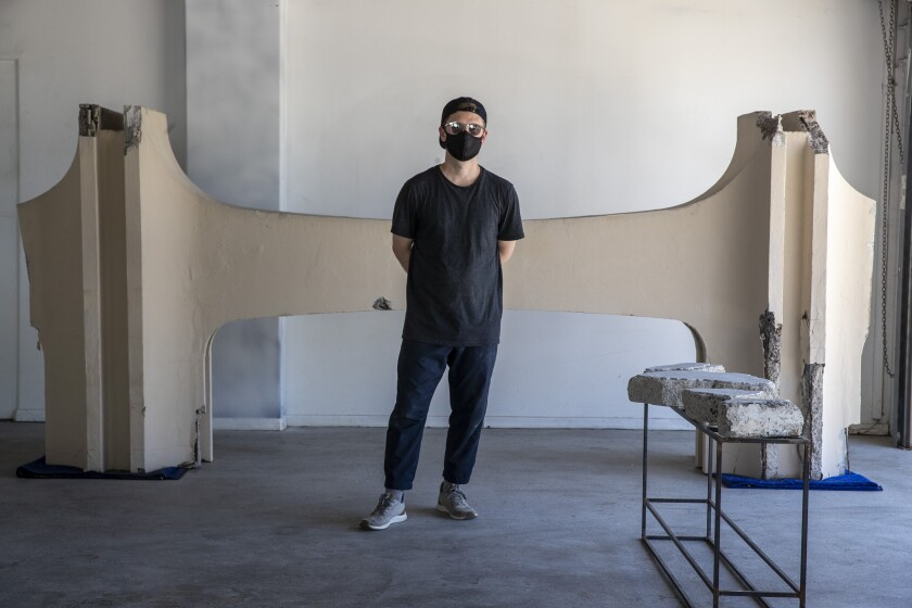 Cayetano Ferrer, dressed in black, stands before an H-shaped fragment of LACMA's Modernist facade.