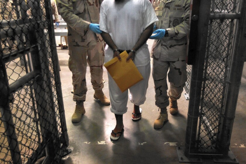 U.S. Navy guards escort a detainee at the Guantanamo Bay naval prison in Cuba.