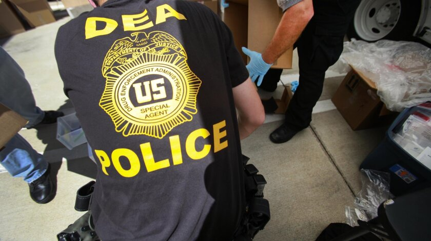DEA agents unload drugs and weapons for a news conference in 2016.