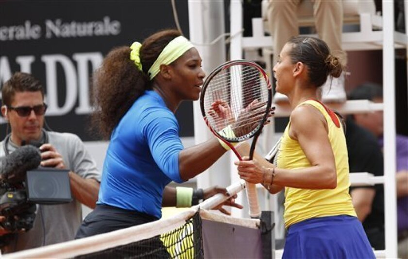 Italy's Flavia Pennetta, right, shakes hands with Serena Williams of the US after retiring from their quarterfinal match at the Italian Open tennis tournament, in Rome, Friday, May 18, 2012. (AP Photo/Alessandra Tarantino)