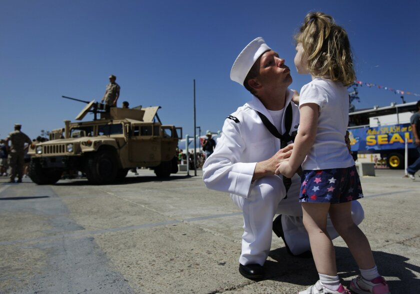 Naval electronic technician Byron Cooke implores his daughter Rebecka, 2, to give him a kiss at the Fleet Week Big Bay Family Festival Saturday. Cooke is a crew member on the USS Freedom, which was open for tours. Photo by James Gregg/San Diego Union Tribune-ZUMA Press.