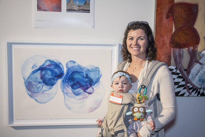 Melissa Moore and Suzanna, recently moved from LA to North County, pose with mom's acrylic ink piece 'Separation 3'