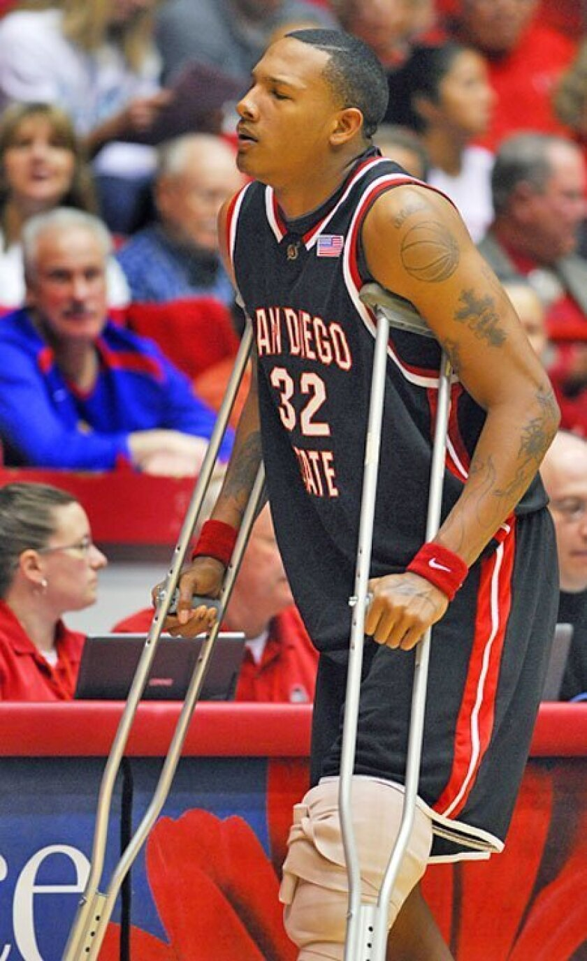 Billy White returns to the bench after getting treatment for a knee injury suffered early in the game. (Associated Press)