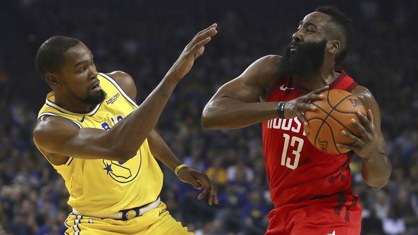 Golden State Warriors' Kevin Durant, left, defends against Houston Rockets' James Harden during the first half.