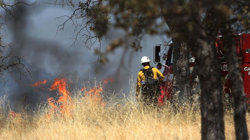 A Tahoe Helitack firefighter approaches the flames near Smartsville, Calif., Tuesday, Aug. 21, 2018.