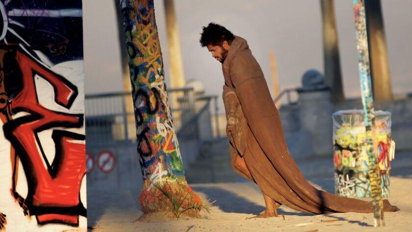 At dawn, a homeless man walks around Venice Beach wearing a blanket .