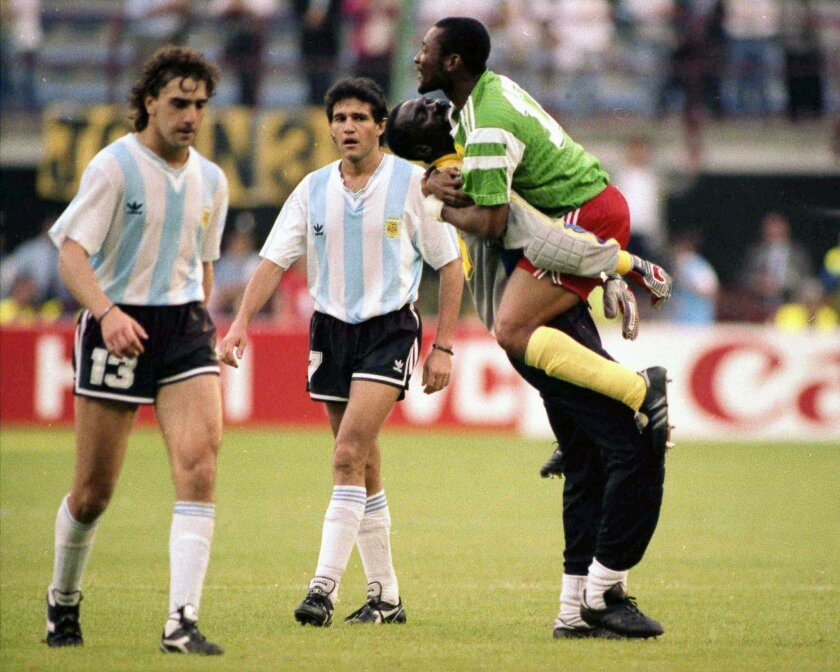 Dejected Argentine players Nestor Lorenzo (left) and Jorge Burruchaga walk off the field past celebrating Cameroon players.