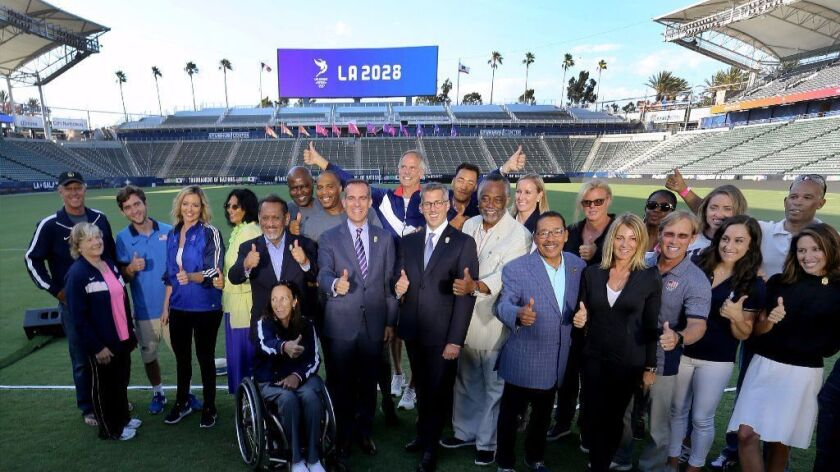 Mayor Eric Garcetti, center, joins officials and former Olympians posing for a photo after a news co