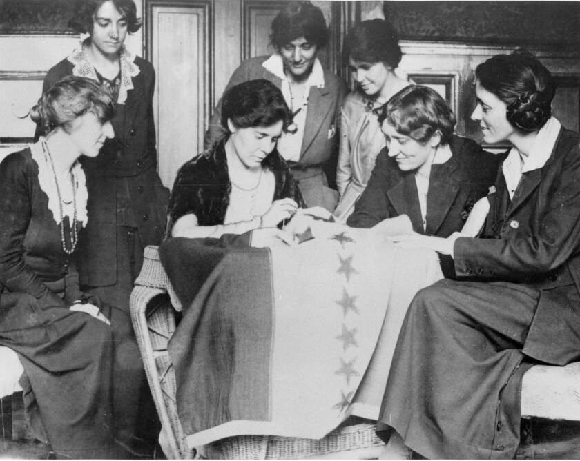 Suffragists celebrating ratification of the woman's right-to-vote amendment in 1920 by sewing stars on a flag, each star representing a state that voted to ratify.