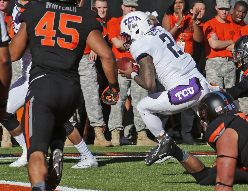 TCU quarterback Trevone Boykin (2) carries the ball into the end zone past Oklahoma State defensive tackle Motekiai Maile (56), for a touchdown in the first quarter of an NCAA college football game in Stillwater, Okla., Saturday, Nov. 7, 2015. (AP Photo/Sue Ogrocki)
