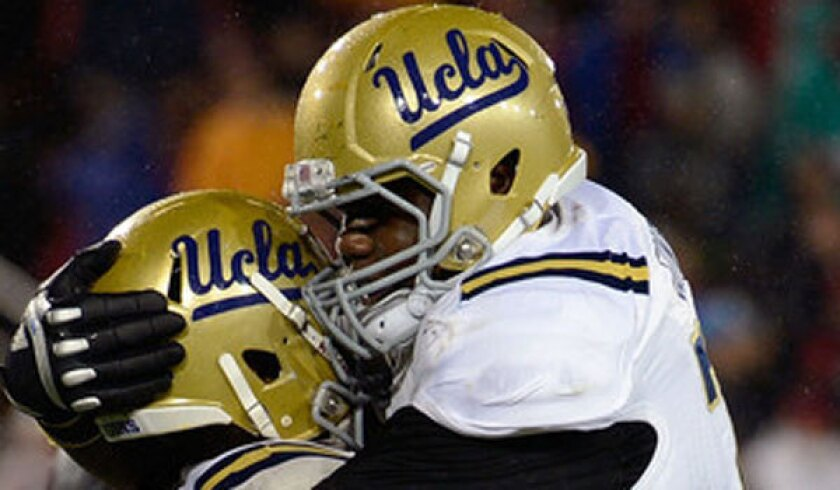UCLA left tackle Simon Goines, right, shown hugging teammate Johnathan Franklin last November, injured his right knee Thursday during a scrimmage.