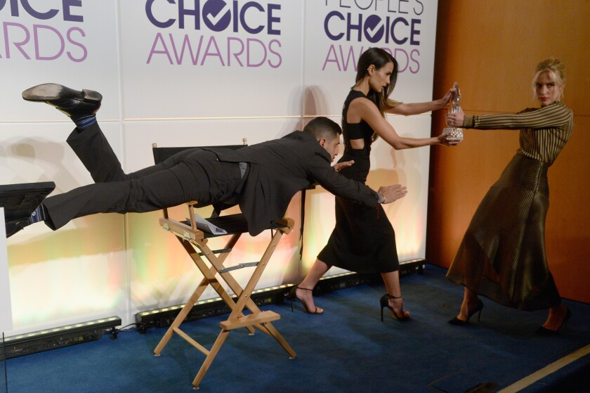 Wilmer Valderrama, Jordana Brewster and Piper Perabo hold the People's Choice Award during the mannequin challenge a news conference in Beverly Hills