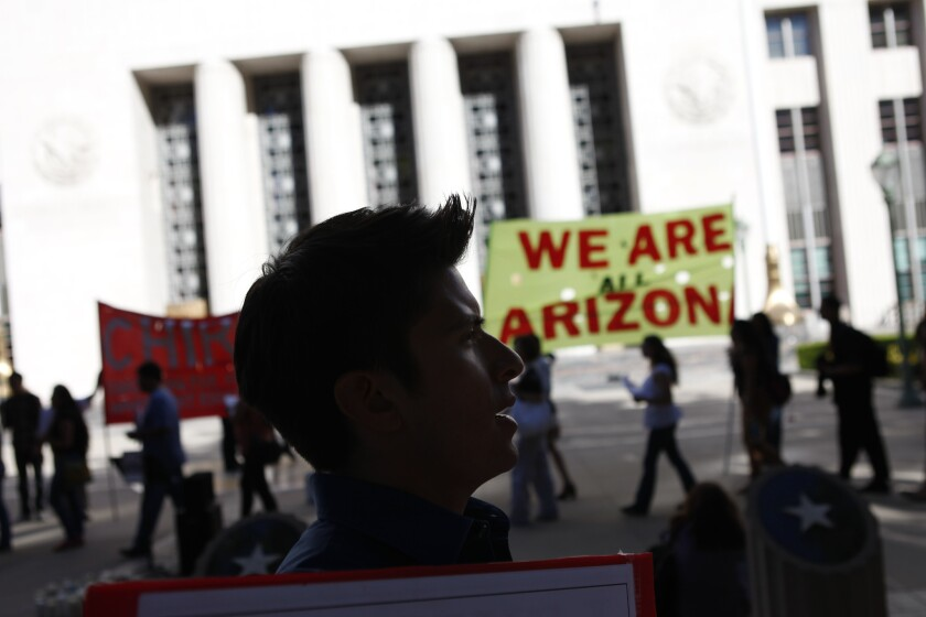 Immigrants' rights supporters march against Arizona's SB 1070 immigration law outside federal court in Los Angeles in 2012.