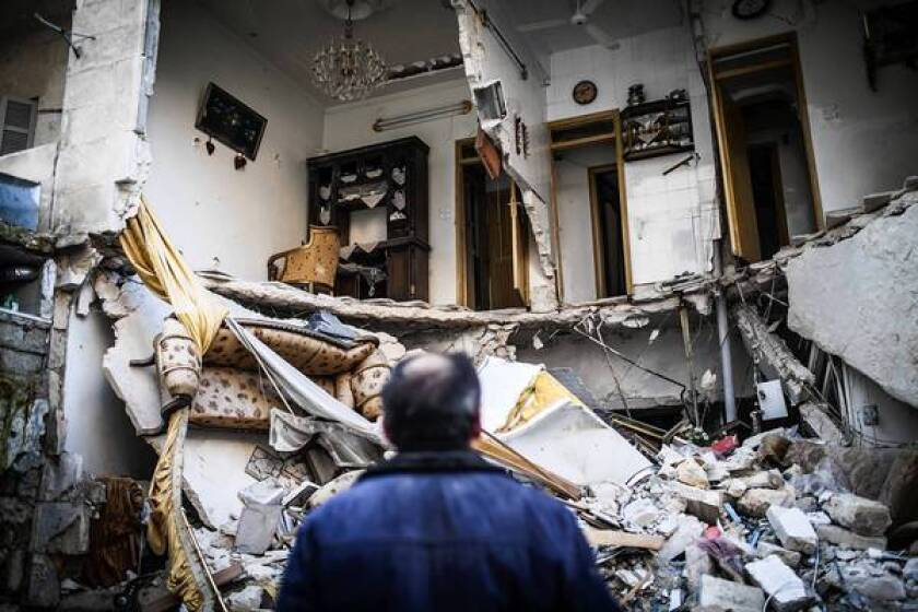 A resident looks at a destroyed home in Aleppo, Syria. The ongoing violence has left some Syrians feeling walled in by the two opposing sides in the conflict.