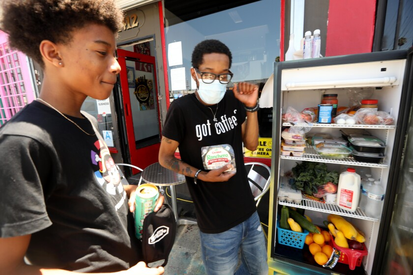 Joshua Mock, at right with son Nolan, owns Little Amsterdam coffee shop in Mid-City. The shop hosts a community fridge.