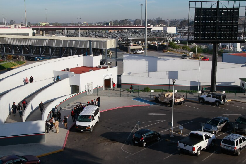 A van with migrants seeking asylum in the U.S. in April at El Chaparral border crossing in Tijuana, Mexico. | (Eduardo Contreras / San Diego Union-Tribune)