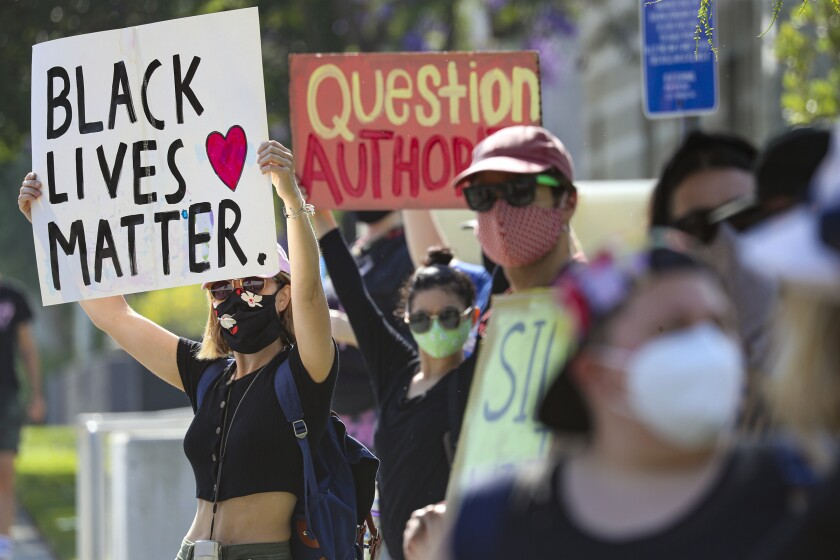 A woman raises a Black Lives Matter sign among a crowd of protesters outside the North Hollywood police station