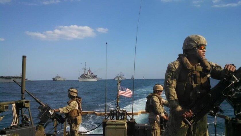 Master at Arms Second Class Linda Phonesaithip (left at gun).  Photo courtesy U.S. Navy