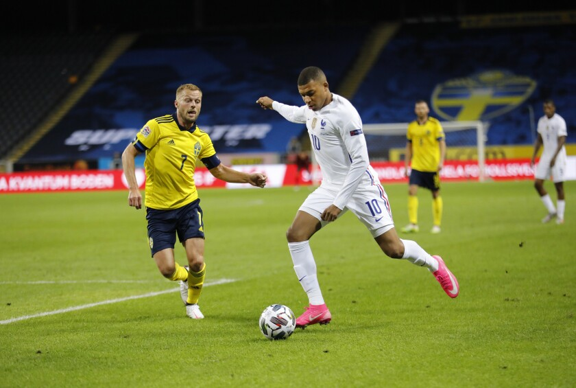 France's Kylian Mbappe, right, scores a goal, and to the left, Sweden's Sebastian Larsson, in action during the UEFA Nations League soccer match between Sweden and France at Friends Arena, Saturday, Sept. 5, 2020, in Stockholm, Sweden. (Christine Olsson/TT via AP)