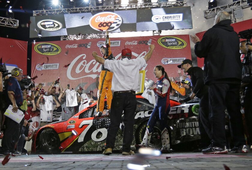 Martin Truex Jr celebrates in Victory Lane after winning the NASCAR Sprint Cup series auto race at Charlotte Motor Speedway in Concord, N.C., Sunday, May 29, 2016. (AP Photo/Chuck Burton)