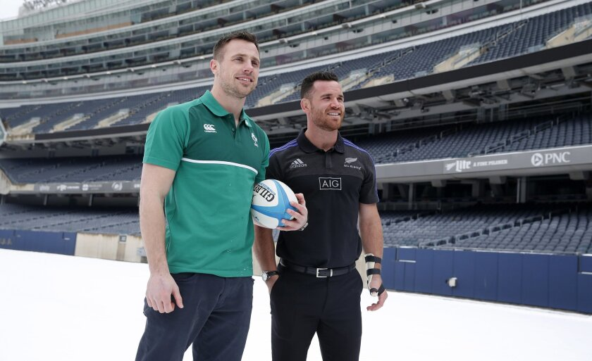 Ireland's Tommy Bowe, left, and New Zealand All Blacks' Ryan Crotty, pose for photographers on the snow covered Soldier Field turf in Chicago, Tuesday, Feb. 16, 2016, after it was announced the teams will play there in November. (AP Photo/Charles Rex Arbogast)